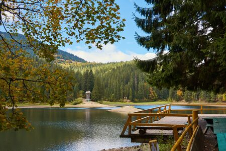 View of Synevir high-altitude lake by autumn day. The leaf fall forest, lake and mountains.
