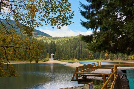 Vue du lac de haute altitude Synevir par jour d'automne. La forêt de chute de feuilles, le lac et les montagnes.