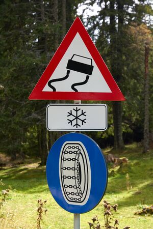 Road signs on a mountain road: warning sign Slippery road surface, mandatory sign Snow chains obligatory, plate Icing. Road rules, Traffic code. Reklamní fotografie