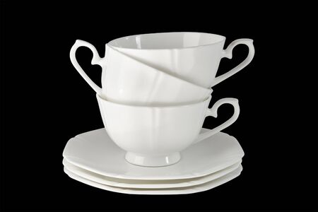 White porcelain cup with a saucer for tea or coffee, demitasse or teacup. Isolated, black background.