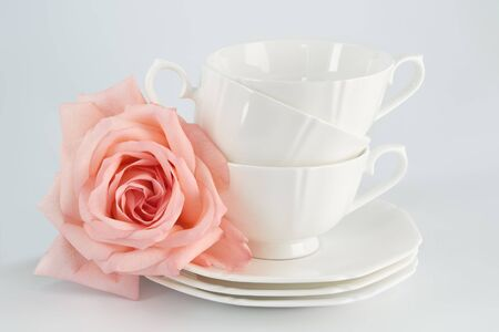 White porcelain cup with a saucer for tea or coffee and pink rose, demitasse or teacup. Crockery on white background.