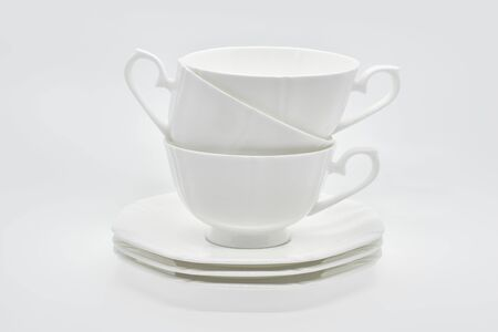 White porcelain cup with a saucer for tea or coffee, demitasse or teacup. Crockery on white background.