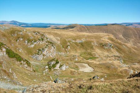 View of Transalpina tourist highway and plateau in mountains of Romania. Tourist mountain road. Autumn mountain landscape.
