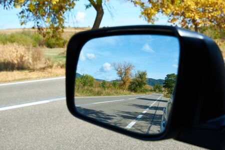 Autumn road in the car mirror. Sunny autumn day and suburban highway. Colorful leaves of trees along the autumn road, colors of leaf-fall. Autumnal landscape.