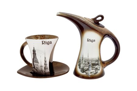 Сeramic teapot and cup and saucer for coffee or tea. Souvenir dishes with the image of the city of Riga. Isolated, white background.