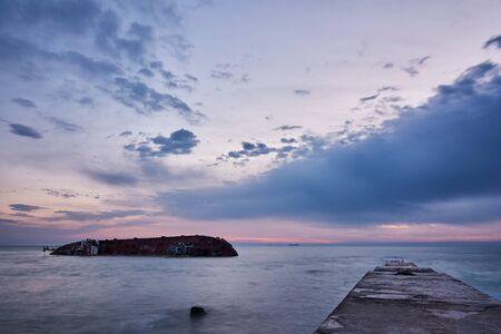 Tanker sunken in a storm near the coast of Odessa, Ukraine. Ship aground near the beach. Landscape at dawn.