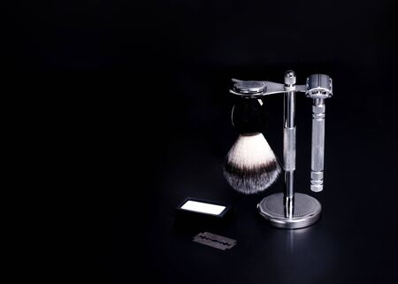 Razor, brush, and blade against a black background