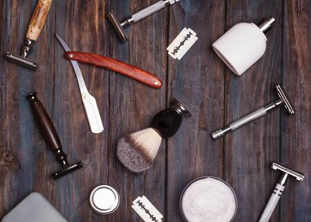 Different kind of razors including safety and straight, blade, brush and perfume on a wooden background. Stock Photo