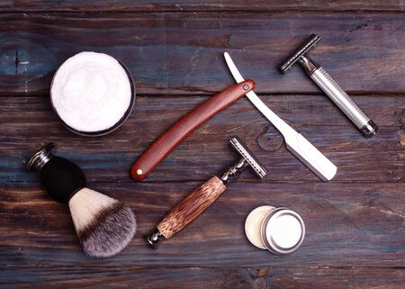 Razors, brush, and balsam on a wood background.