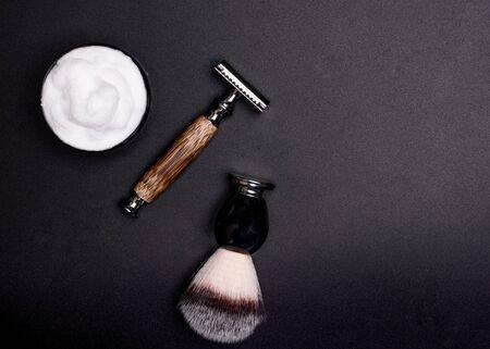 Razor, brush, and shaving foam on a black background.
