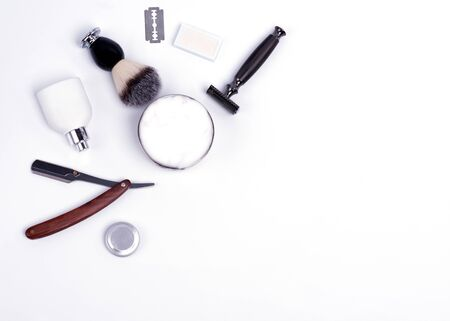 Razor, brush, blade, balsam, shaving foam and perfume on a white background.