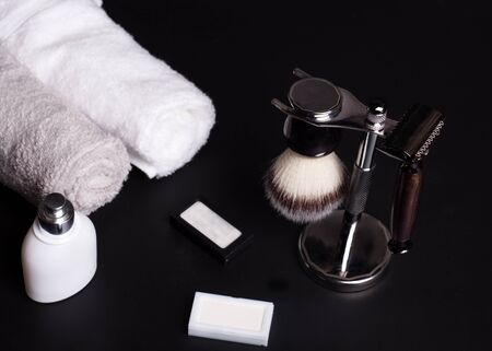 Razor, brush, blade and towels on a black background.