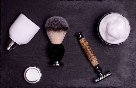 Razor, brush, perfume, balsam and shaving foam on a black background. Stock fotó