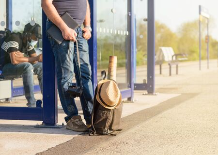 Green travel backpack, hat, maps, glasses on the platform at the  train station during quarantine and  man in the background at the sunset 版權商用圖片
