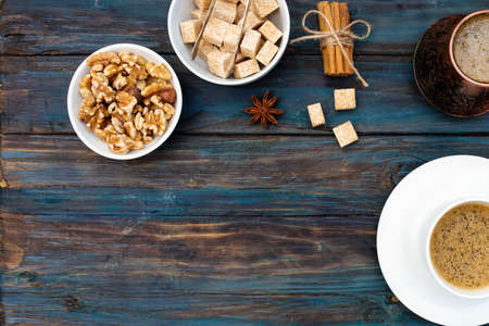 Nuts in the bowl, coffeepot, cinnamon, anise, sugar and cap of coffee on wooden background