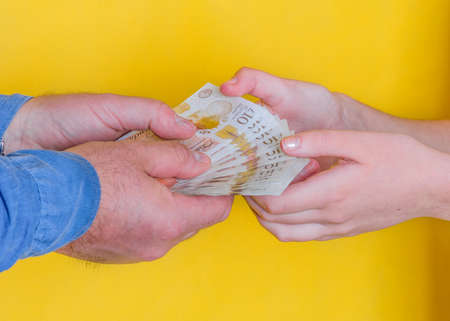 people passing money each other on yellow background Banco de Imagens