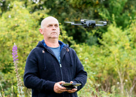 a man launching a drone on a meadow