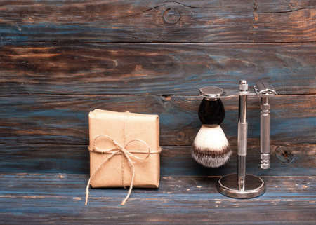 Razor and brush on stand and gift on a wooden background.