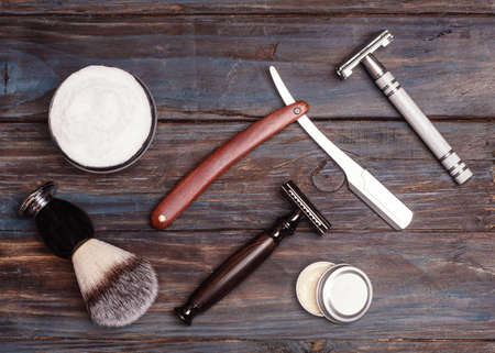 Razors, brush, balsam and foam on a wood background.