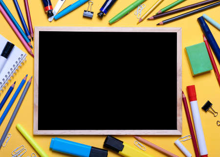 Mockup of Black board, pencils, highlighters, chalks on yellow background
