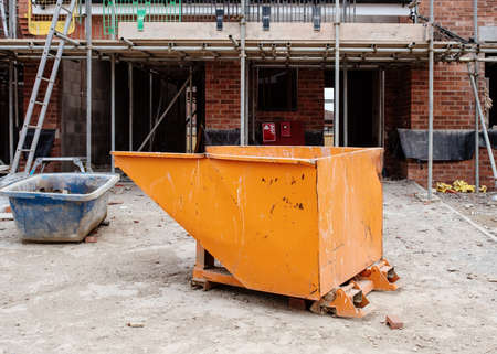 Combi Forklift Tipping Skip on construction site in front of new house Standard-Bild