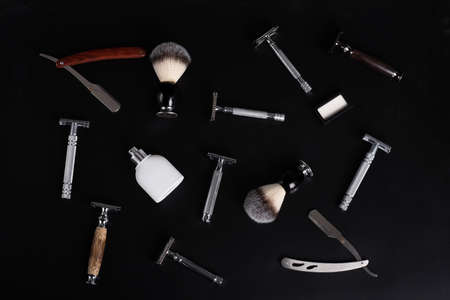 Razor and brush on stand, towels, perfume, balsam and blades on a black background.