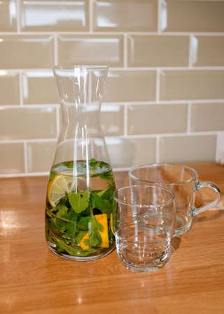 fresh water with lemon and mint in decanter and glass on table in kitchen
