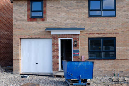 An ordinary new house for sale and blue recycling skip in front of it