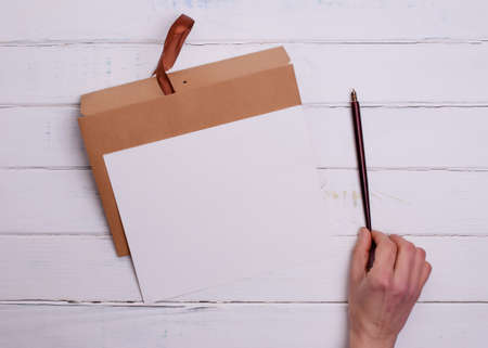 One Craft envelop, white paper t and ink pencil in hand on white wooden background