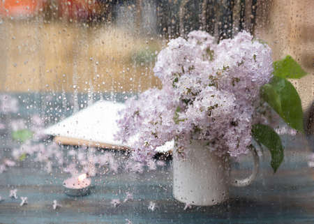a white mug with lilac, a candle and an envelope on a vintage wooden surface on spring raining day. View from outside.