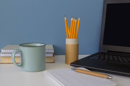 Front view on modern creative workspace. Laptop with black screen, blue cup of coffee, yellow pencils on reusable paper tube on white table. Home office of a creative entrepreneur or student