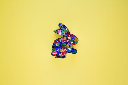 Rabbit bunny shaped form for gingerbread or cookies decorated with colorful stars sparkles inside on yellow background with copy space for your creative design. Easter concept