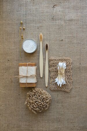 Set of natural bathroom and home spa tools. Zero waste. Ecotolls toothbrushes, bamboo swabs, soap, dry shampoo, toothpowder, jute washcloth on fabric background with copy space, vertical composition