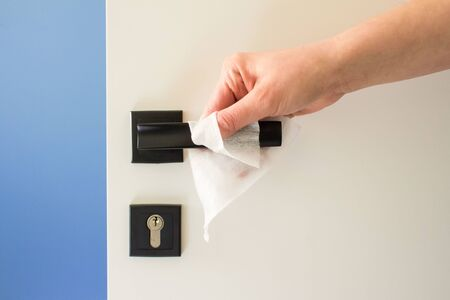 Close up of woman hand cleaning door handle with disinfectant wet pipe, disinfecting household surfaces against viruses or bacteria. Recommendations and guidelines, prevention of flue disease