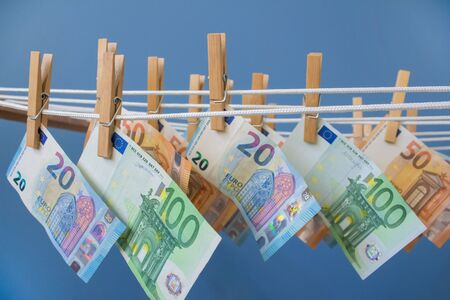 Money laundering concept. Euro money banknotes hung out to dry hanging on clotheslines pin with clothespins on blue trendy background