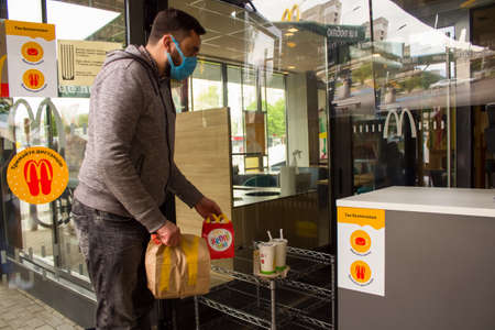 Lviv, Ukraine - May 17, 2020 : McDonalds restaurant, man picking up his order contactlessly. Healthcare and social distance concept, reopening