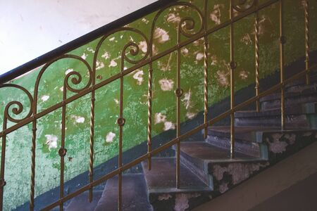 Classic traditional vintage metal baluster against aged green wall in abandoned historical building in Lviv, Ukraine Stockfoto