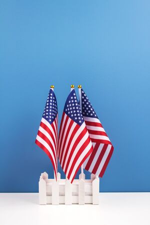 Vertical composition with three american flags on white table with trendy blue wall background. National symbolic of USA - flag Old Glory. Flag Day and Independence Day celebration concept Imagens