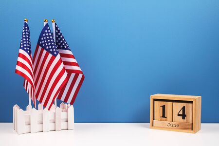 Set of three american flags with date June 14th on wooden bricks on white table with blue wall background. National symbolic of USA - flag Old Glory. USA Flag Day celebration concept
