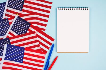 Top view on set of american flags, red and blue pens and empty notebook with copyspace for text on light blue background, national symbol of USA - flag Old Glory. Business or education concept