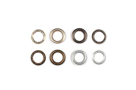Set of brass multicoloured metal eyelets or rivets - curtains rings for fastening fabric to the cornice, isolated on white with copyspace for text for your presentation Foto de archivo