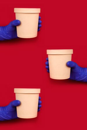 Vertical composition with hands wearing blue disposable protective gloves on red background holding round paper food container - cardboard cup for soup or other dishes takeaway. Copyspace, mockup
