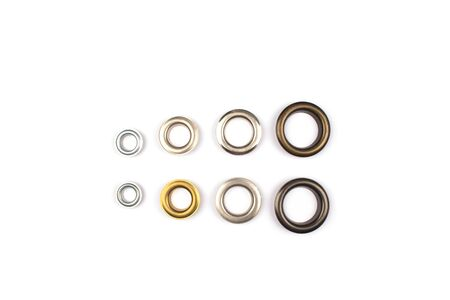 Set of brass multicoloured metal eyelets or rivets - curtains rings for fastening fabric to the cornice, isolated on white with copyspace for text for your presentation