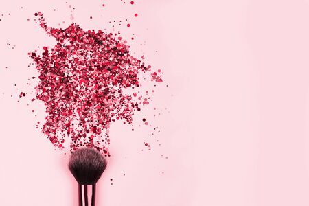 Closeup of professional cosmetic makeup brush with explosion of shiny pink colorful sparkles on bright pink background with copyspace for your text. Creative make-up concept
