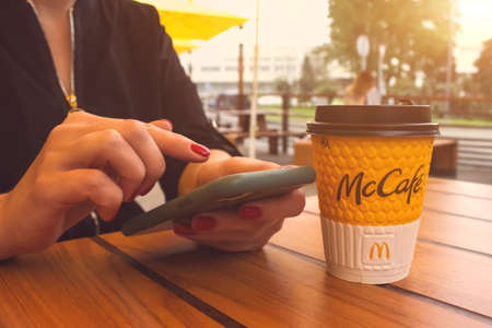 Lviv, Ukraine - June 14, 2020 : young woman with perfect manicure scrolling feed with fresh news or social media and drinking coffee during breakfast or lunch at McDonald's restaurant. Early morning