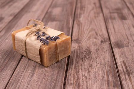 Bars of natural herbal handmade soap with lavender extract on natural wooden background with copyspace. Home spa treatments. Natural cosmetics concept
