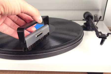 Mans hand cleaning vinyl with special brush - turntable vinyl record player, vintage record player. Trends in music concept. Sound technologies for DJ to mix and play music. Mockup image