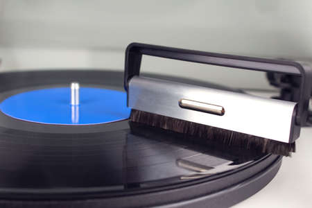 Cleaning vinyl with special brush - turntable vinyl record player, vintage record player. Trends in music concept. Sound technologies for DJ to mix and play music. Mockup image