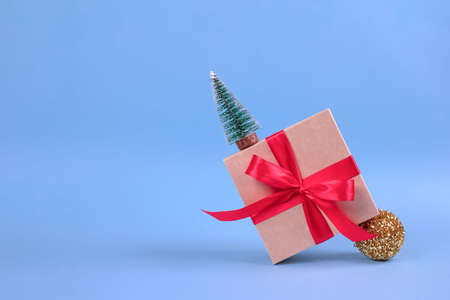 Banner with gift box with red bow and Christmas tree decorations on festive blue background with blurred bokeh and copyspace for your text. Christmas or New Year celebration concept