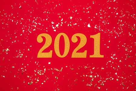 Festive background with 2021. Golden numbers on red background with holographic sparkles around - Happy New Year celebration concept. Christmas holidays 2021 celebration